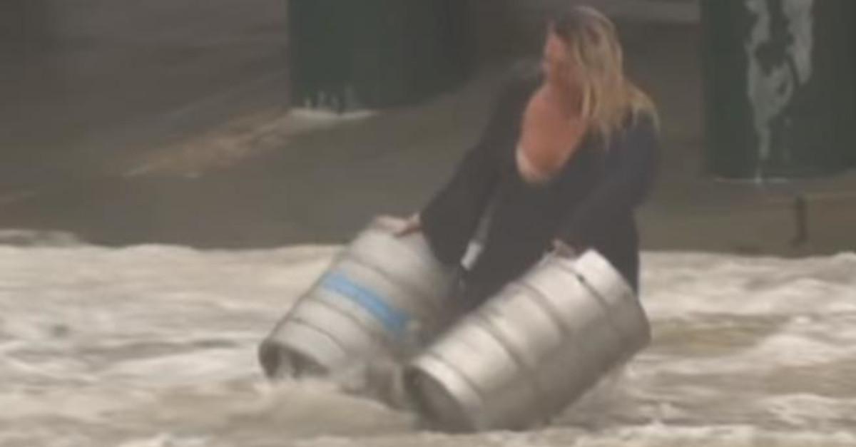 Una donna australiana scende in una strada allagata per salvare due fusti di birra